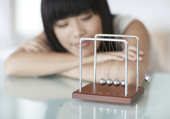 Woman Looking at Newton's Cradle