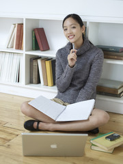 Mid Adult Woman Reading Books and Writing in Notebook