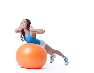 Pretty sportswoman exercising with orange ball