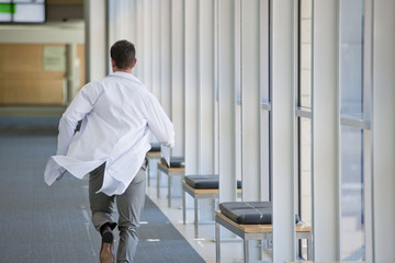 Doctor running down hospital corridor