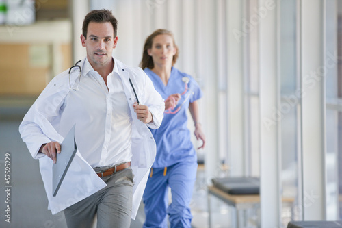Doctor and nurse running down hospital corridor