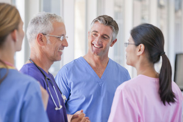 Smiling doctors and nurse talking