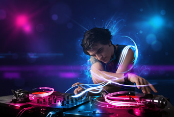 Disc jockey playing music with electro light effects and lights