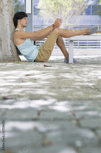 Young man with digital tablet sitting on sidewalk with foot on bench