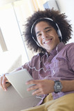 Portrait of smiling young man wearing headphones and using digital tablet