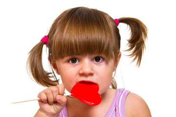 little girl eating red heart lollipop