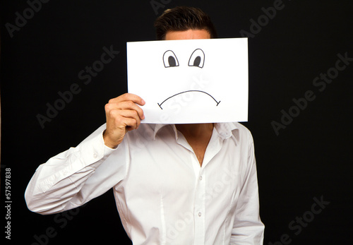Young businessman holding card with a angry face