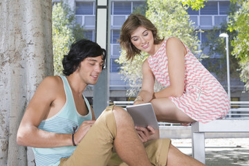 Young couple using digital tablet in urban park