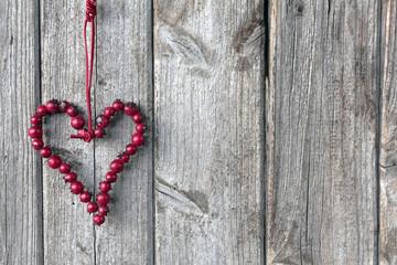 Herz aus roten Beeren an grauer Bretterwand