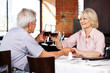 Elderly couple clink glasses in restaurant