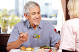 Senior man talking to woman while eating