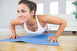 Young fit woman doing press ups on an exercise mat