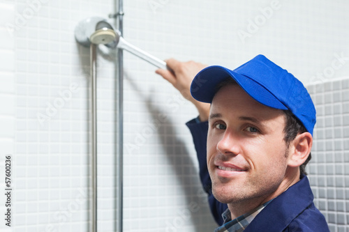 Cheerful plumber repairing shower head