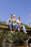 Portrait of smiling multi-generation family sitting barefoot on footbridge over stream