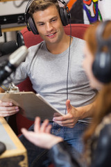 Attractive radio host interviewing a guest holding clipboard