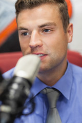 Well dressed concentrating radio host moderating