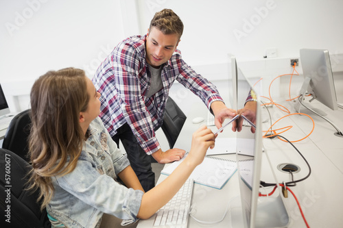 Two happy students working on computer pointing at it