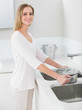 Cheerful gorgeous woman filling pan with water