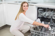 Smiling gorgeous model kneeling next to dish washer