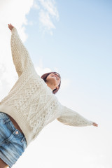 Woman in white sweater and denim shorts stretching her arms agai