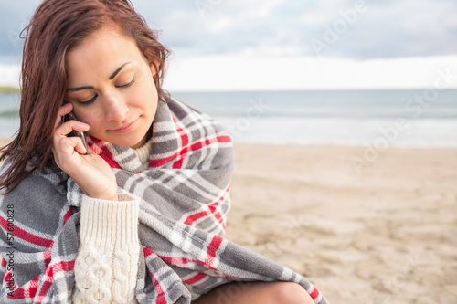 Woman covered with blanket using cellphone at beach