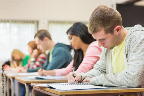 Young students writing notes in classroom - 57600871