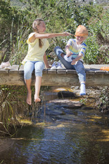 Boy and girl playing with fishing net on footbridge over stream