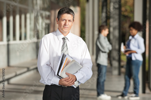 Confident Professor With Books Standing On College Campus