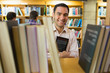 Smiling mature student holding book by shelf with men at library