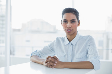 Stern chic businesswoman looking at camera while sitting at her