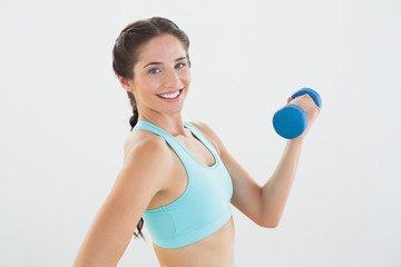 Side view portrait of a smiling woman with dumbbell