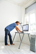 Mann steht barfuß am PC