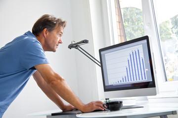 Mann  schaut sich am Computer Statistik an