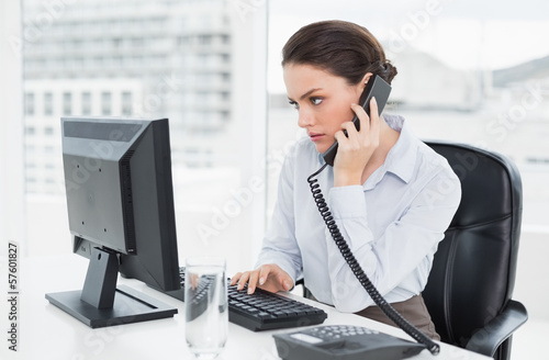 Elegant businesswoman using landline phone and computer in offic