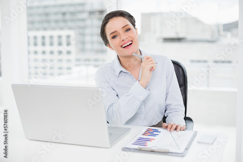 Happy businesswoman with graphs and laptop in office