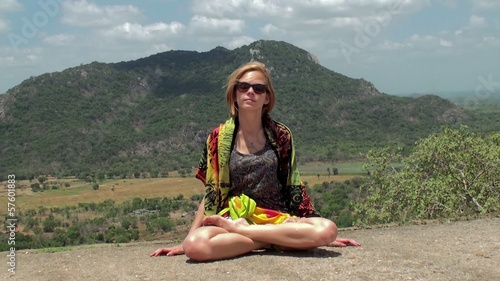 The girl  is sitting on top of a mountain.
