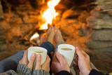 Hands holding coffee cups in front of lit fireplace