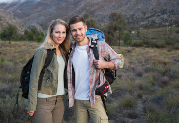 Couple with backpacks standing on forest landscape
