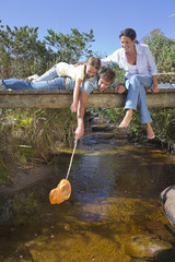 Family laying on footbridge and dipping fishing net in stream