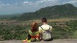 Young couple of tourists sits in the wind on top of a mountain.