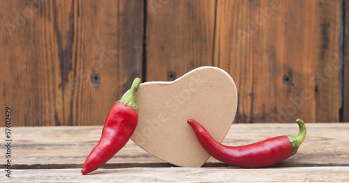 red chilly peppers with cardboard heart on wood background