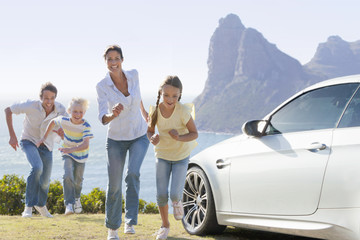 Happy family running outside car near ocean