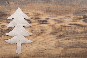 christmas tree made of gray cardboard on wooden background