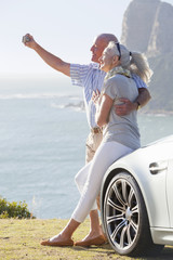 Couple leaning against car and taking self-portrait with camera near ocean