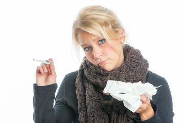 Blonde Frau hält ein Fieberthermometer