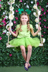 Happy little girl with shamrocks on head sit on swing