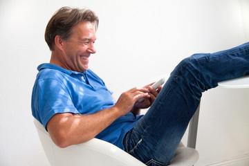 Älterer Mann mit Telefon in der Hand, lachend
