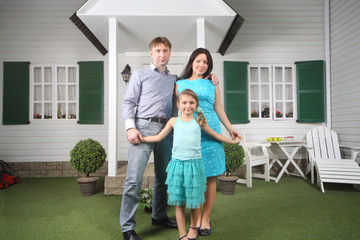 Smiling father, mother and daughter stand near porch
