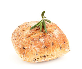 Whole wheat bun with seeds and a sprig of rosemary.