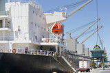 Grab bucket unloading grain from bulk tanker in commercial dock